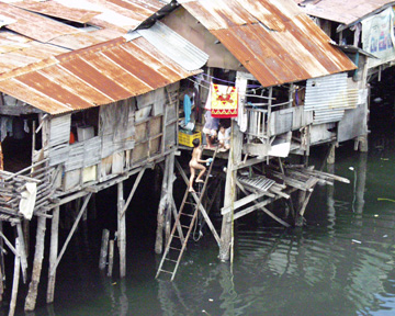 """A boy climbs a ladder to his """"home"""" after bathing in the dirty river.  I took this photo in Cebu."""