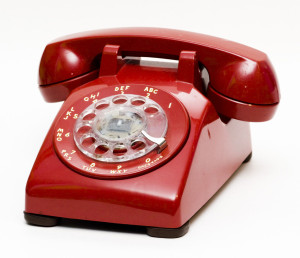 An red rotary phone from the 1960's or 1970's.